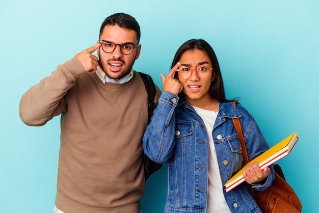 Junge gemischte studentenpaare isoliert auf blauem hintergrund, die eine enttäuschungsgeste mit dem zeigefinger zeigen.