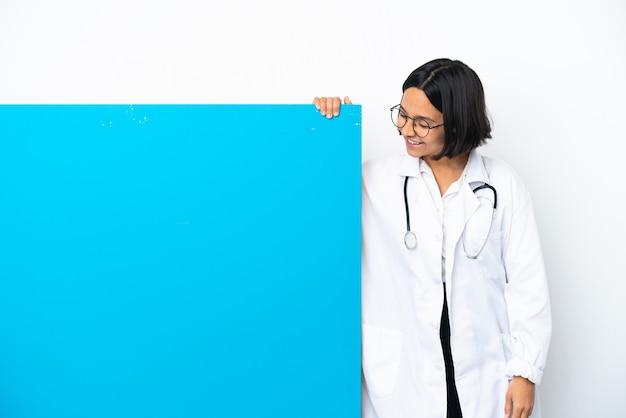 Junge gemischtrassige ärztin mit einem großen plakat isoliert auf weißem hintergrund, das beim nachschlagen eine idee denkt
