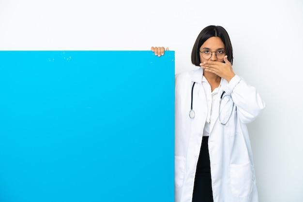 Junge gemischtrassige ärztin mit einem großen plakat isoliert auf weißem hintergrund, das den mund mit den händen bedeckt