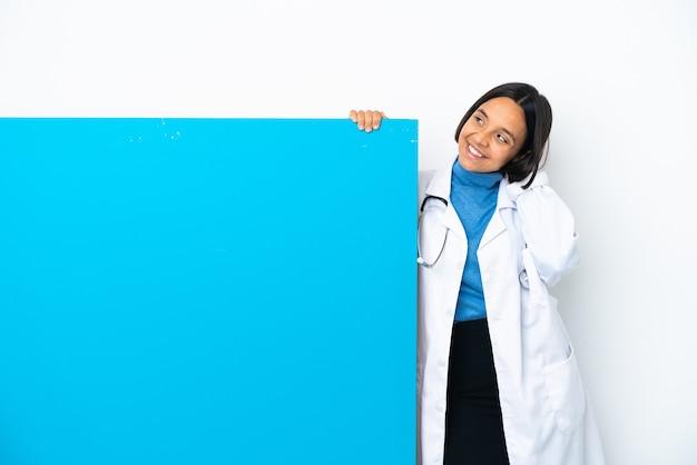 Junge gemischtrassige ärztin mit einem großen plakat isoliert auf weißem hintergrund, das eine idee denkt