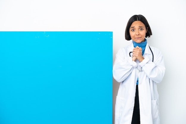 Junge gemischtrassige ärztin mit einem großen plakat isoliert auf weißem hintergrund lachen