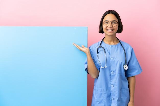 Junge gemischtrassige chirurgin mit einem großen banner über isoliertem hintergrund, der kopienraum imaginär auf der handfläche hält, um eine anzeige einzufügen