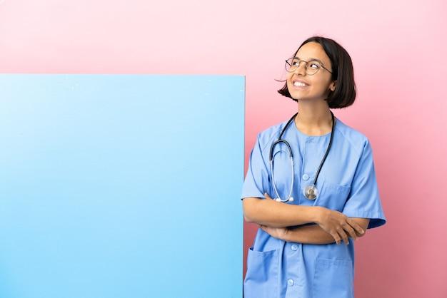 Junge gemischtrassige chirurgin mit einem großen banner über isoliertem hintergrund, die eine idee denkt, während sie nach oben schaut