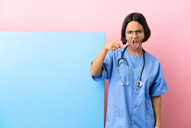 Junge gemischtrassige chirurgin mit einem großen banner über isoliertem hintergrund frustriert und zeigt nach vorne