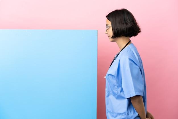 Junge gemischtrassige chirurgin mit einem großen banner über isoliertem hintergrund in rückenposition und im rückblick