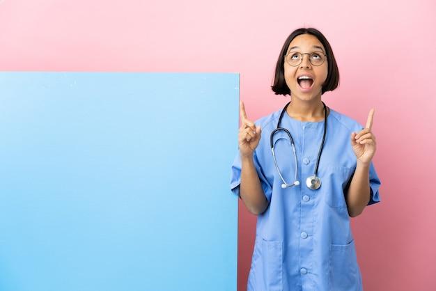 Junge gemischtrassige chirurgin mit einem großen banner über isoliertem hintergrund überrascht und zeigt nach oben