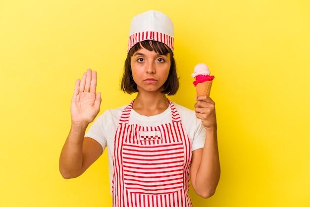 Junge gemischtrassige eismaschine frau, die ein eis auf gelbem hintergrund hält, das mit ausgestreckter hand steht und ein stoppschild zeigt, um sie zu verhindern.