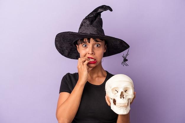 Junge gemischtrassige frau, die als hexe verkleidet ist und einen schädel hält, der auf violettem hintergrund isoliert ist und fingernägel beißt, nervös und sehr ängstlich.