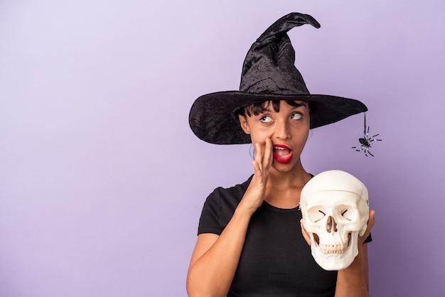 Junge gemischtrassige frau, die als hexe verkleidet ist und einen schädel isoliert auf violettem hintergrund hält, sagt eine geheime heiße bremsnachricht und schaut beiseite