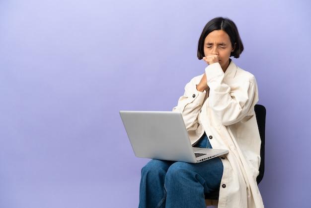 Junge gemischtrassige frau, die auf einem stuhl mit laptop sitzt und viel hustet