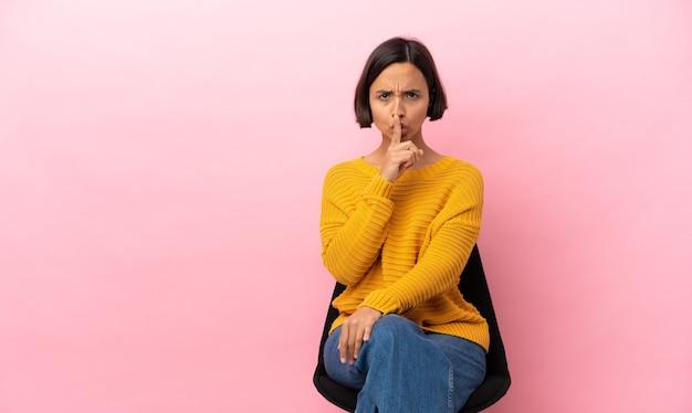 Junge gemischtrassige frau, die auf einem stuhl sitzt, isoliert auf rosafarbenem hintergrund, zeigt ein zeichen der stille geste, die den finger in den mund steckt