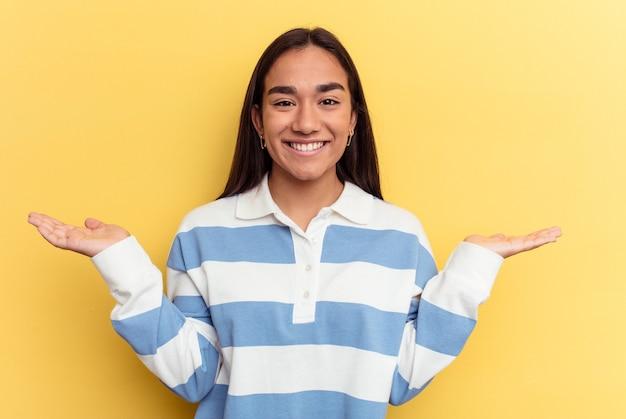 Junge gemischtrassige frau, die auf gelbem hintergrund isoliert ist, macht mit armen skaliert, fühlt sich glücklich und selbstbewusst.