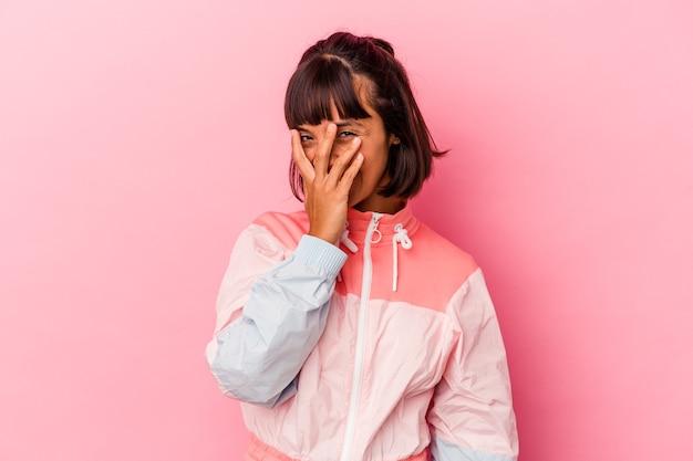 Junge gemischtrassige frau, die auf rosafarbenem hintergrund isoliert ist, blinzelt durch die finger in die kamera, verlegen das gesicht.