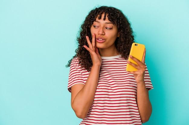Junge gemischtrassige frau, die ein mobiltelefon isoliert auf blauem hintergrund hält, sagt eine geheime heiße bremsnachricht und schaut beiseite