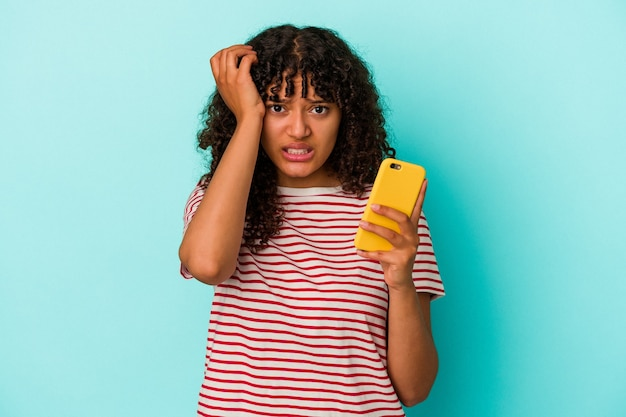 Junge gemischtrassige frau, die ein mobiltelefon isoliert auf blauem hintergrund hält und schockiert ist, hat sich an ein wichtiges treffen erinnert.