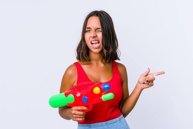 Junge gemischtrassige frau, die eine wasserpistole hält, die isoliert mit den zeigefingern auf einen kopienraum zeigt und aufregung und verlangen ausdrückt.