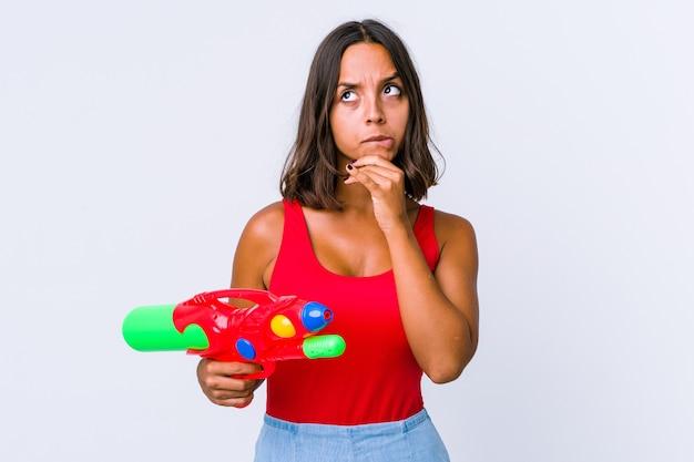 Junge gemischtrassige frau, die eine wasserpistole hält, isoliert nachdenklich, plant eine strategie und denkt über die art und weise eines unternehmens nach.