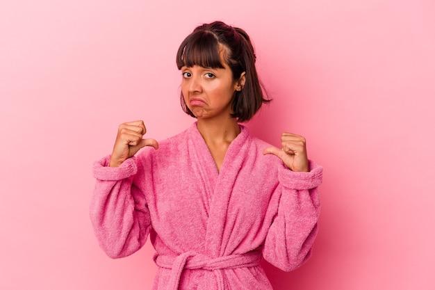 Junge gemischtrassige frau, die einen bademantel einzeln auf rosafarbenem hintergrund trägt, fühlt sich stolz und selbstbewusst, beispiel zu folgen