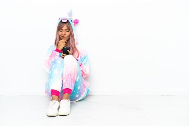 Junge gemischtrassige frau, die einen einhorn-pyjama trägt, der auf dem boden sitzt, isoliert auf weißem hintergrund denkt und eine nachricht sendet