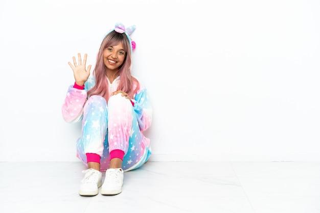 Junge gemischtrassige frau, die einen einhorn-pyjama trägt, der auf dem boden sitzt, isoliert auf weißem hintergrund, der mit den fingern fünf zählt
