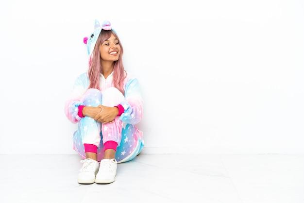 Junge gemischtrassige frau, die einen einhorn-pyjama trägt, der auf dem boden sitzt, isoliert auf weißem hintergrund, der seitlich schaut
