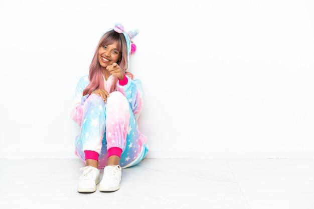 Junge gemischtrassige frau, die einen einhorn-pyjama trägt, der auf dem boden sitzt, isoliert auf weißem hintergrund, zeigt mit einem selbstbewussten ausdruck mit dem finger auf dich