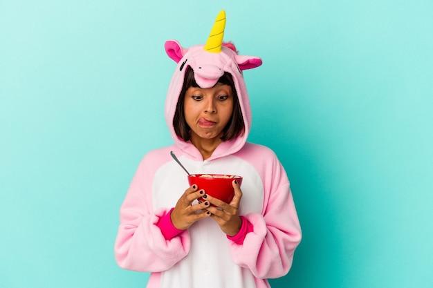 Junge gemischtrassige frau, die einen einhorn-pyjama trägt und ein getreide auf blauem hintergrund hält