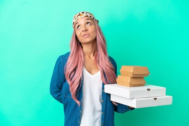 Junge gemischtrassige frau, die pizza und burger auf grünem hintergrund hält und nach oben schaut