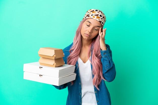 Junge gemischtrassige frau, die pizza und burger auf grünem hintergrund mit kopfschmerzen isoliert hält
