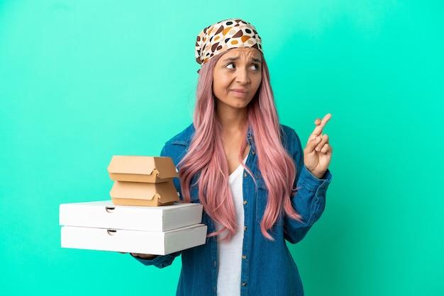 Junge gemischtrassige frau, die pizza und burger einzeln auf grünem hintergrund hält, mit gekreuzten fingern und das beste wünscht