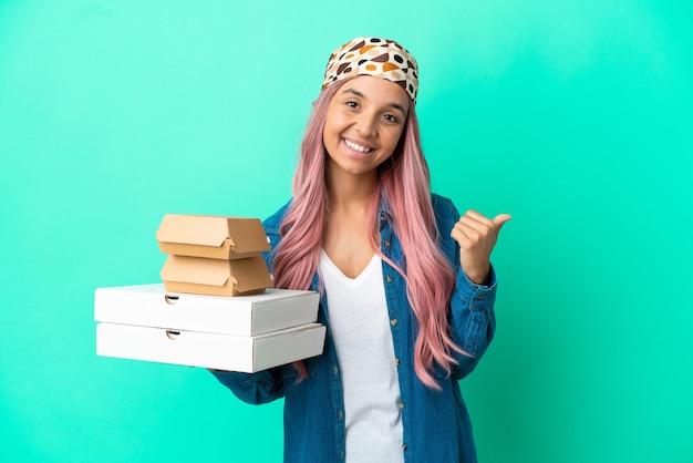 Junge gemischtrassige frau, die pizza und burger einzeln auf grünem hintergrund hält und auf die seite zeigt, um ein produkt zu präsentieren
