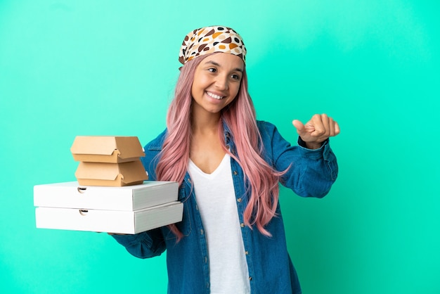 Junge gemischtrassige frau, die pizza und burger einzeln auf grünem hintergrund hält und eine geste mit dem daumen nach oben gibt