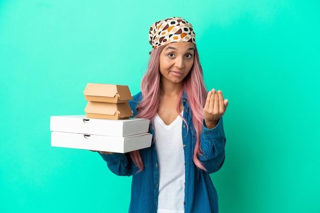 Junge gemischtrassige frau, die pizza und burger einzeln auf grünem hintergrund hält und einlädt, mit der hand zu kommen. schön, dass du gekommen bist