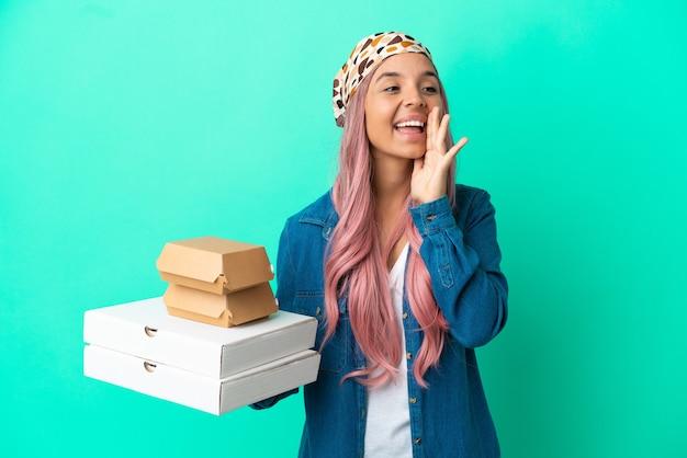 Junge gemischtrassige frau, die pizza und burger einzeln auf grünem hintergrund hält und mit weit geöffnetem mund zur seite schreit