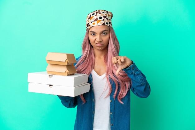 Junge gemischtrassige frau, die pizza und burger isoliert auf grünem hintergrund hält und daumen nach unten mit negativem ausdruck zeigt
