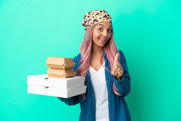 Junge gemischtrassige frau, die pizza und burger isoliert auf grünem hintergrund hält und einen finger zeigt und hebt