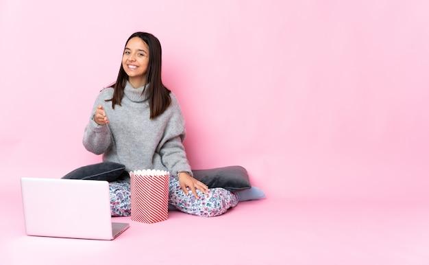 Junge gemischtrassige frau, die popcorn isst, während sie einen film auf dem laptop sieht, der sich die hände schüttelt, um ein gutes geschäft abzuschließen?