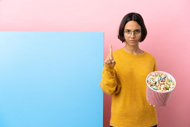 Junge gemischtrassige frau, die popcorn mit einem großen banner über isoliertem hintergrund hält, der eins mit ernstem ausdruck zählt