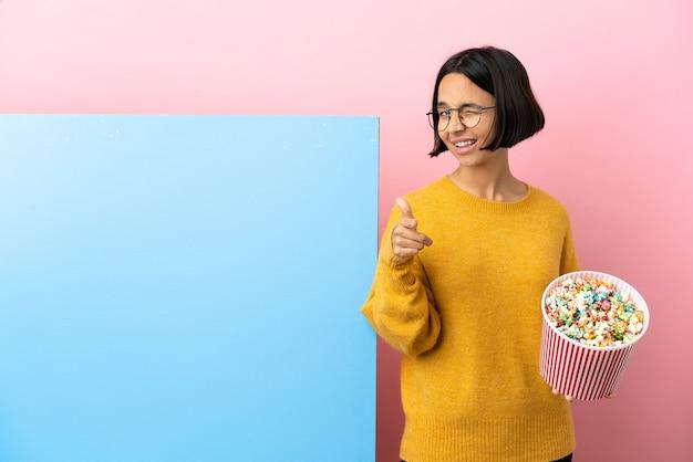 Junge gemischtrassige frau, die popcorn mit einem großen banner über isoliertem hintergrund hält, der nach vorne zeigt und lächelt