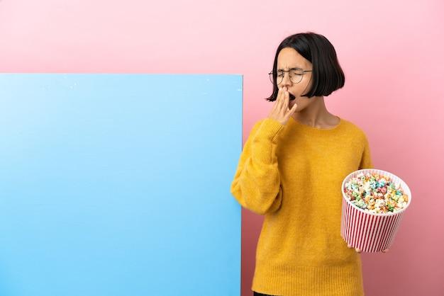 Junge gemischtrassige frau, die popcorn mit einem großen banner über isoliertem hintergrund hält, gähnt und den weit geöffneten mund mit der hand bedeckt