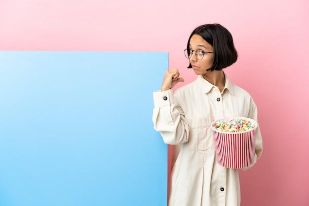 Junge gemischtrassige frau, die popcorn mit einem großen banner über isoliertem hintergrund hält, stolz und selbstzufrieden