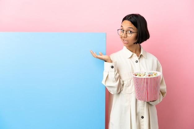 Junge gemischtrassige frau, die popcorn mit einem großen banner über isoliertem hintergrund hält und die hände zur seite ausstreckt, um einzuladen, zu kommen