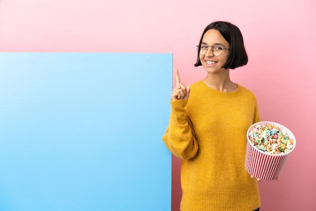 Junge gemischtrassige frau, die popcorn mit einem großen banner über isoliertem hintergrund hält und einen finger im zeichen des besten zeigt und hebt
