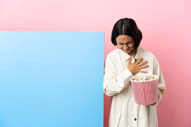 Junge gemischtrassige frau, die popcorn mit einem großen banner über isoliertem hintergrund hält und einen schmerz im herzen hat