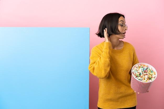 Junge gemischtrassige frau, die popcorn mit einem großen banner über isoliertem hintergrund hält und etwas hört, indem sie die hand auf das ohr legt