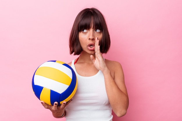 Junge gemischtrassige frau, die volleyball auf rosafarbenem hintergrund spielt, sagt eine geheime heiße bremsnachricht und schaut beiseite
