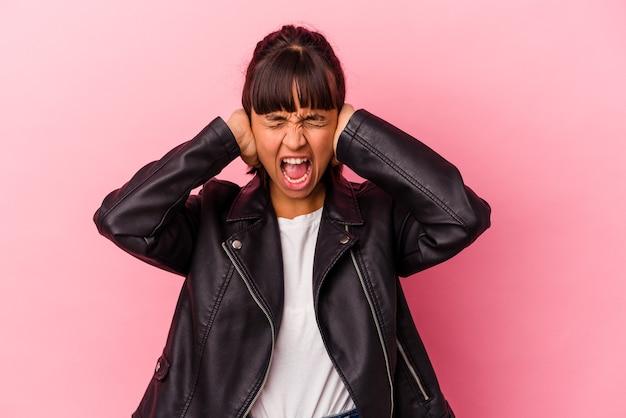 Junge gemischtrassige frau einzeln auf rosafarbenem hintergrund, die ohren mit händen bedeckt, die versuchen, nicht zu laute geräusche zu hören.