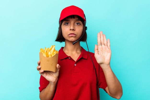 Junge gemischtrassige frau fast-food-restaurant-arbeiter, die pommes auf blauem hintergrund isoliert hält und mit ausgestreckter hand mit stoppschild steht und sie verhindert.