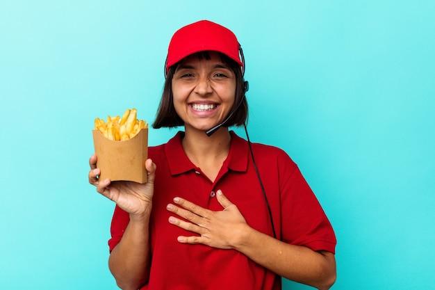 Junge gemischtrassige frau fast-food-restaurantarbeiterin, die pommes auf blauem hintergrund isoliert hält, lacht laut und hält die hand auf der brust.