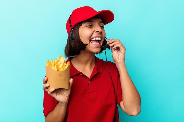 Junge gemischtrassige frau fast-food-restaurantarbeiterin, die pommes auf blauem hintergrund isoliert hält, schreit und palm in der nähe des geöffneten mundes hält.